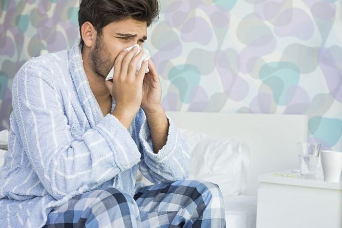 Sick man blowing his nose in tissue paper on bed at home